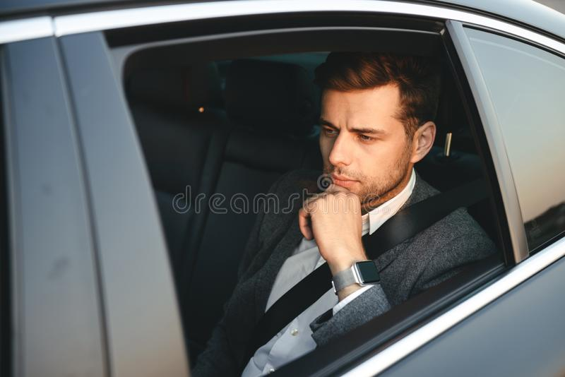 Portrait of serious caucasian man wearing businesslike suit, back sitting while riding in car with safety belt. Portrait of serious caucasian man wearing stock photos