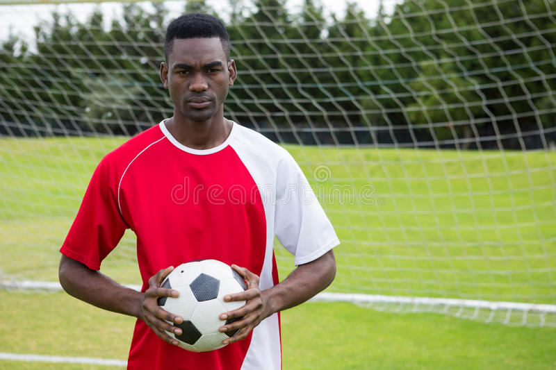 Portrait of serious confident male soccer player holding ball royalty free stock image