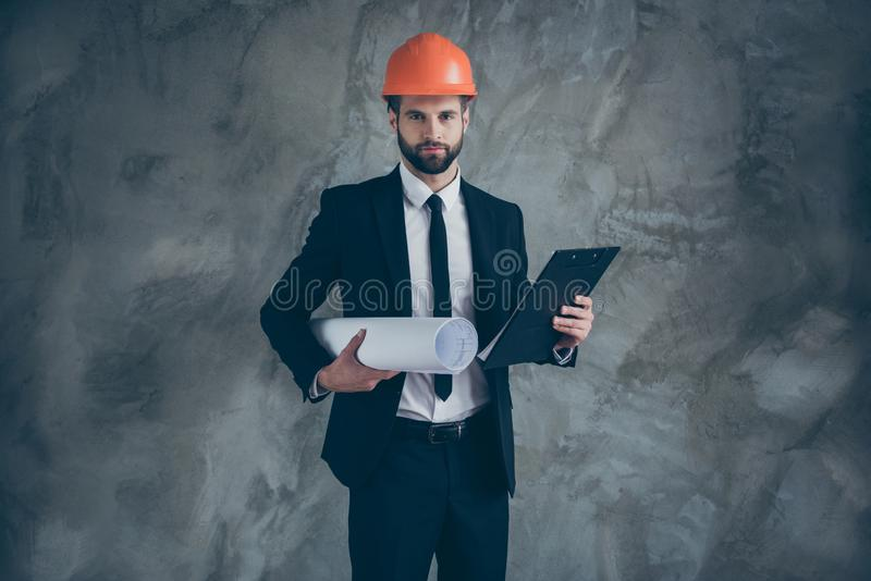 Portrait of serious confident man worker architect hold blueprint clipboard want organize builders job wear black trendy royalty free stock image