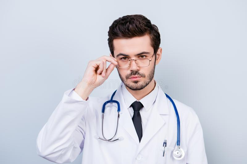 Portrait of serious confident young doctor touching his glasses. Close up portrait of serious handsome trainee. Touching eyeglasse stock photography