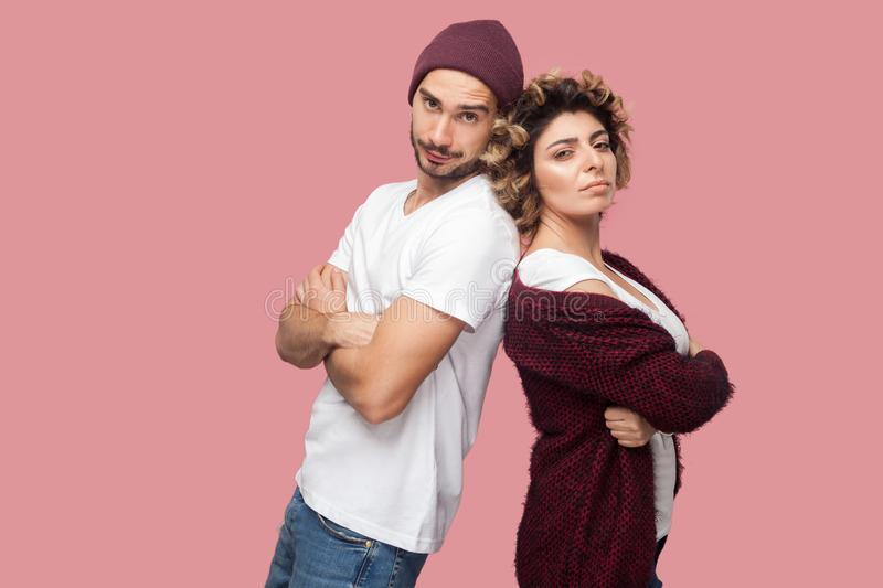 Portrait of serious couple of friends in casual style standing back to back, crossing arms and looking at camera with proud face royalty free stock images