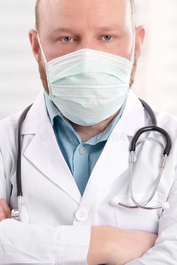 Portrait of a serious doctor wearing surgical face mask and stethoscope royalty free stock photography