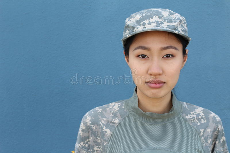 Portrait of serious female army soldier against blue background.  stock photography