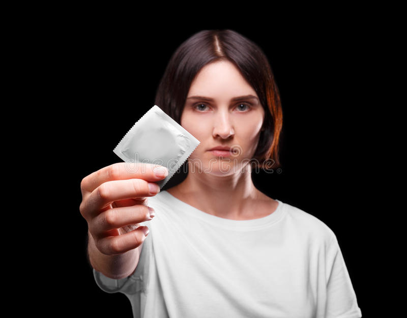 A close-up of a serious young woman showing a packed condom on a black background. Healthy lifestyle concept. Copy space royalty free stock photo