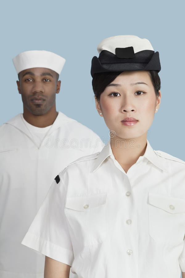 Portrait of serious female US Navy officer in front male sailor over light blue background stock photography