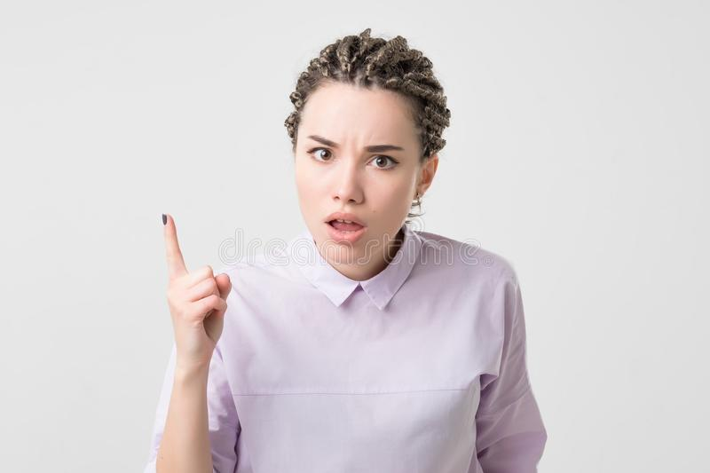 Portrait of serious, frowning, angry, grumpy young woman with african braids pointing finger upwards, scolding someone royalty free stock photos