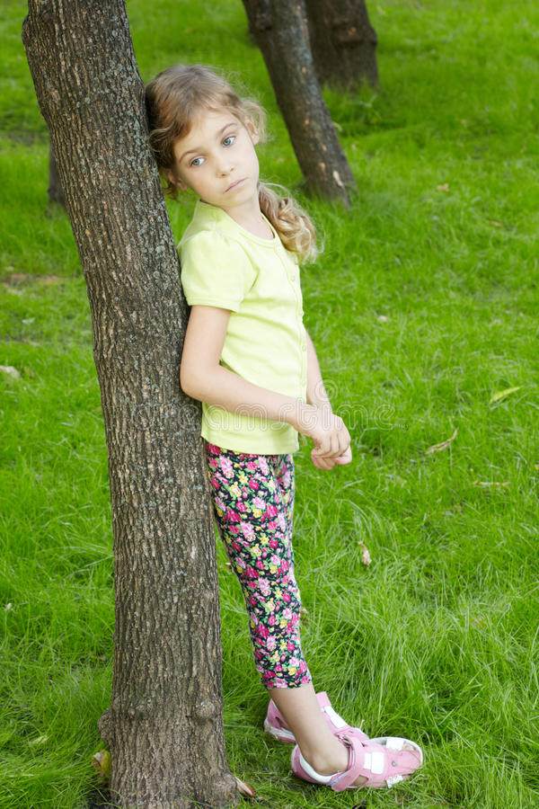 Portrait of serious girl, that stands in park stock photography