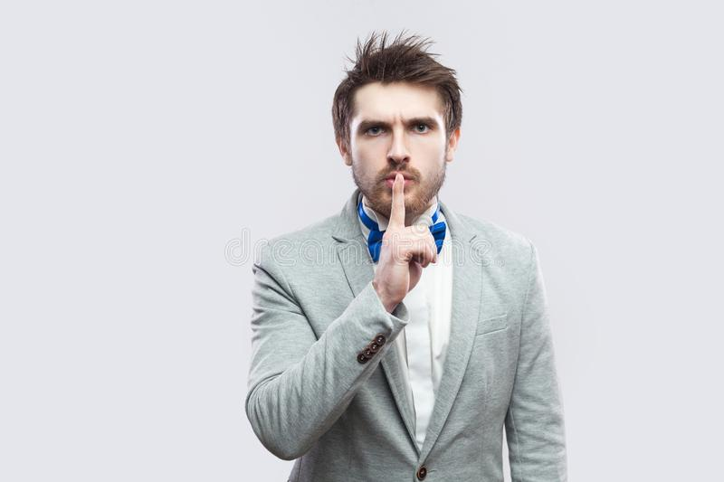 Portrait of serious handsome bearded man in casual grey suit and blue bow tie standing, looking at camera with silence sign royalty free stock photography