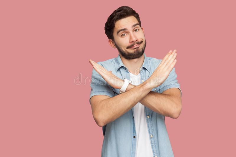 Portrait of serious handsome bearded young man in blue casual style shirt standing with X sign hands and looking at camera. Indoor studio shot, isolated on stock photos