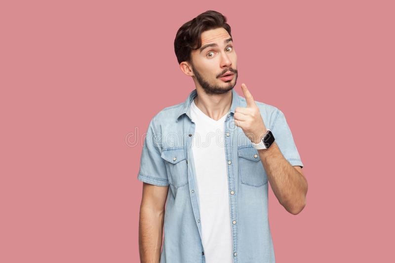 Portrait of serious handsome bearded young man in blue casual style shirt standing with warming sign and looking at camera to give royalty free stock images