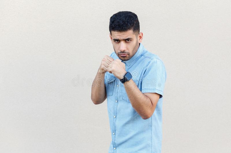 Portrait of serious handsome young bearded businessman in blue shirt standing with boxing fists and ready to attack and looking at stock images