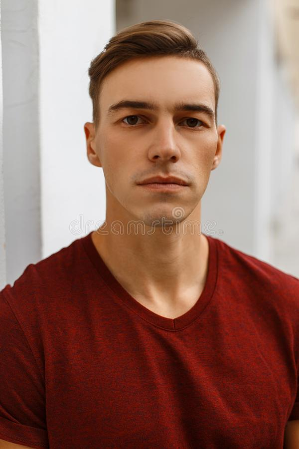 Portrait of a serious handsome young man in a fashionable red t-shirt with a stylish hairstyle near a vintage white building. royalty free stock images