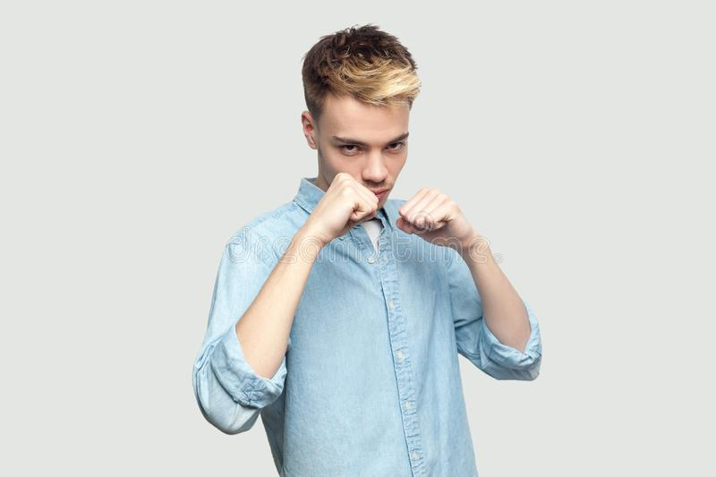 Portrait of serious handsome young man in light blue shirt standing in boxing fists, looking at camera and ready to attack or. Defence. indoor studio shot on royalty free stock photo