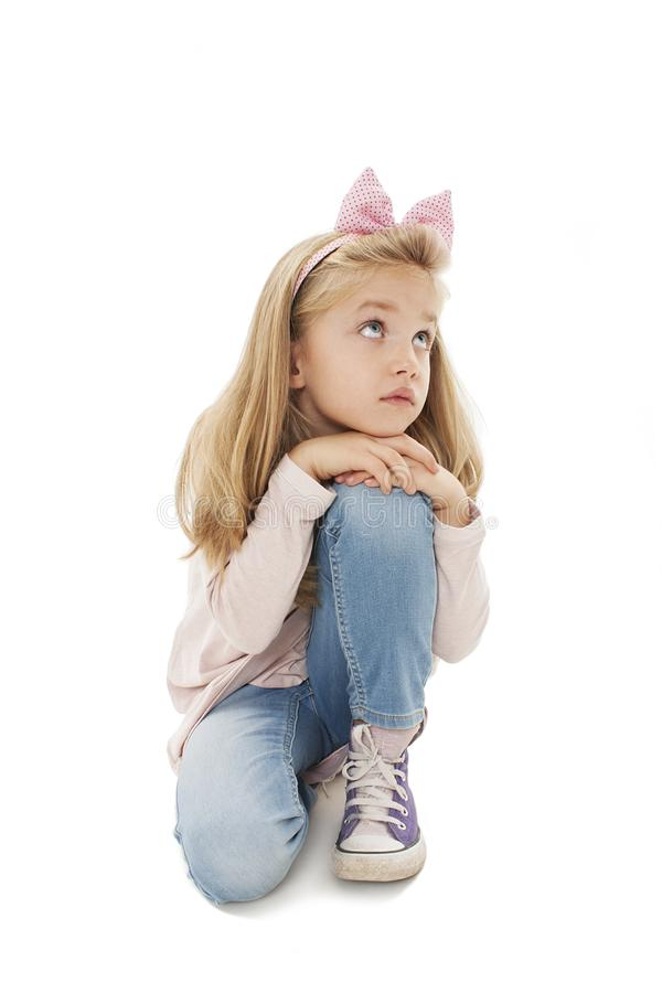 Portrait of a serious little girl sitting on the knees, looking up stock photos