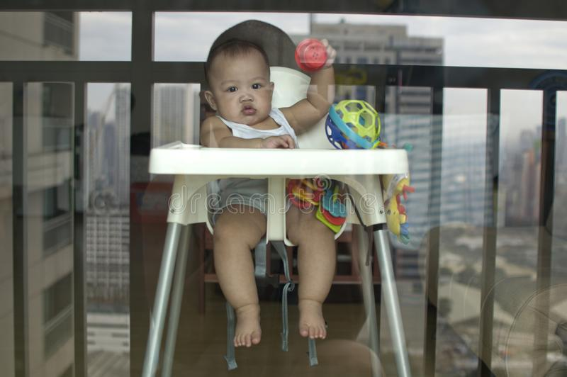A portrait of a serious looking baby boy. While sitting in a high chair stock image