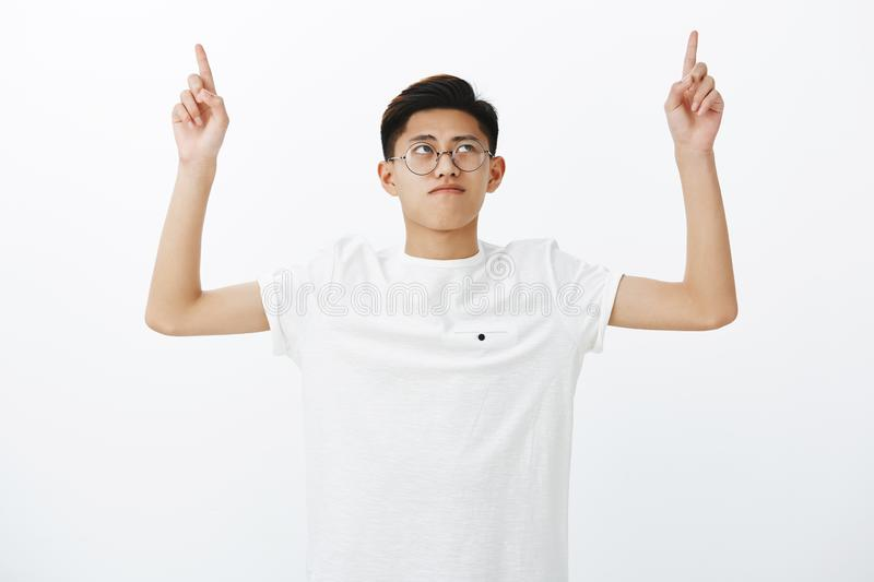 Portrait of serious-looking charming young chinese male student in white t-shirt raising hands, pointing and looking up stock image