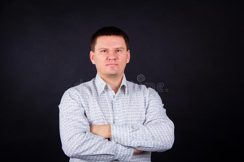Portrait of serious man on black background. Brutal man in a shirt with arms crossed on his chest. An inflated man in a light shir stock photo
