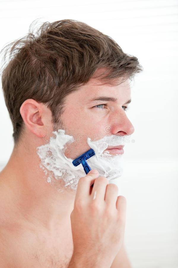 Portrait Of A Serious Man Shaving In The Bathroom Stock Image