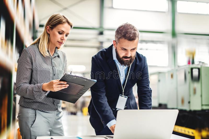 A portrait of an industrial man and woman engineer with laptop in a factory, working. A portrait of a serious mature industrial men and women engineer with royalty free stock images