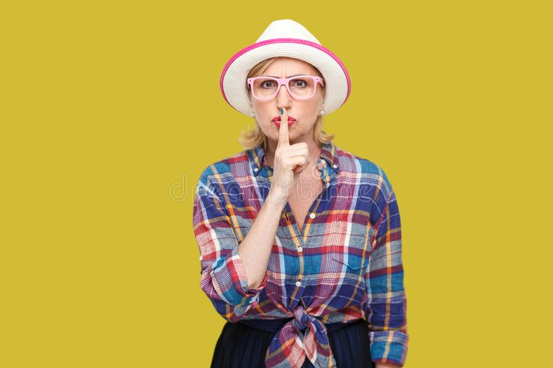 Portrait of serious modern stylish mature woman in casual style with hat and eyeglasses standing with silence sign and asking to. Be quiet. indoor studio shot royalty free stock photo