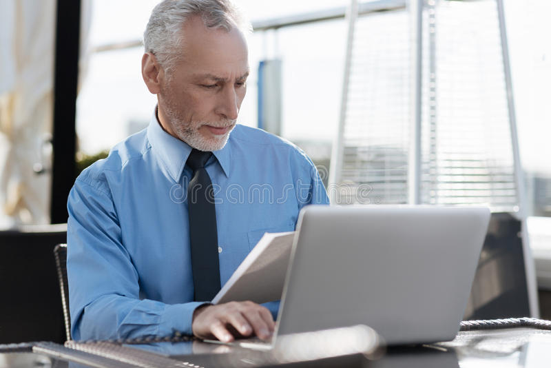 Portrait of serious office worker while sitting at his workplace. Just attention. Confident bearded man looking at documents and wrinkling forehead while reading royalty free stock images