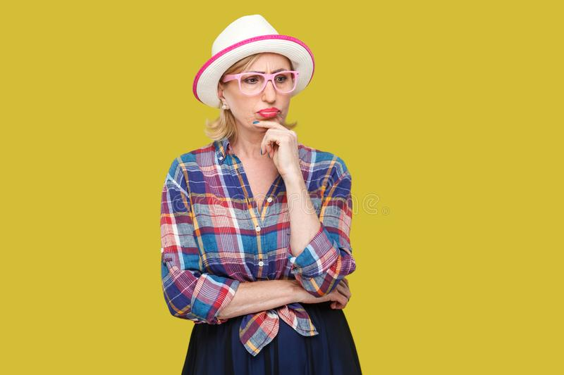 Portrait of serious pensive modern stylish mature woman in casual style with hat and eyeglasses standing, looking away and. Pondering doubtful. indoor studio stock image
