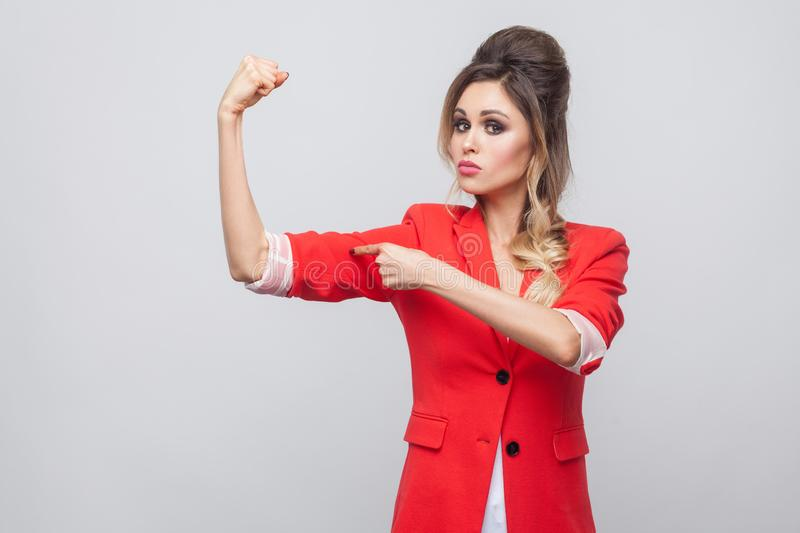 Portrait of serious proud beautiful business lady with hairstyle and makeup in red fancy blazer, standing, looking at camera and. Pointing her bicep. indoor stock photography