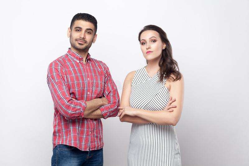 Portrait of serious proud handsome man in red checkered shirt and beautiful woman in white striped dress standing and looking at royalty free stock image