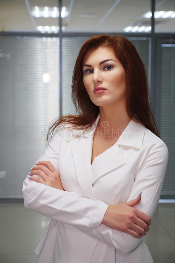 Portrait of serious redhead businesswoman in white suit in office stock image