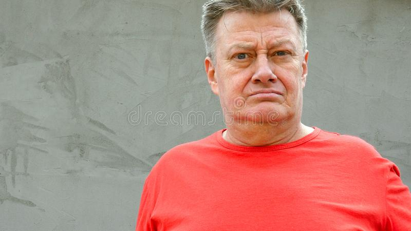 Portrait of serious senior adult man in red t-shirt, who is looking at  camera. Against background of gray plastered wall in the. Style of loft design. Close-up royalty free stock photo