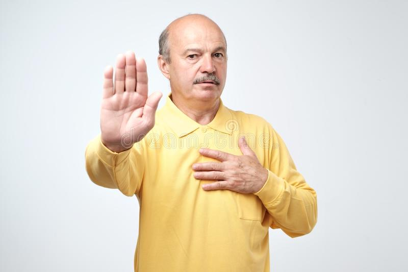 Portrait of a serious senior man showing stop gesture with his palm stock photo