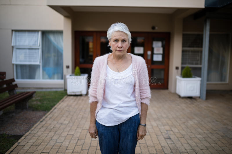 Portrait of serious senior woman standing on entrance stock images