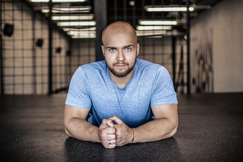 Portrait of a serious sports coach with a bald head. resting in the gym after push-ups. workout was successful. dressed in a. Portrait of a serious sports coach royalty free stock photo