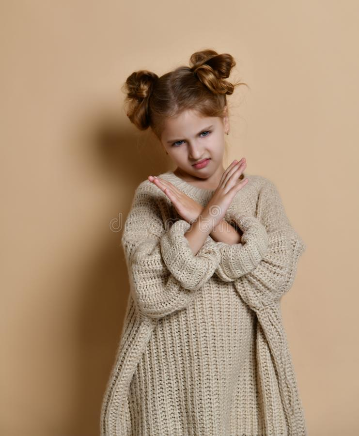 Portrait of serious, unhappy kid girl holding two arms crossed, gesturing no sign, looking away camera. Isolated on beige background royalty free stock photos