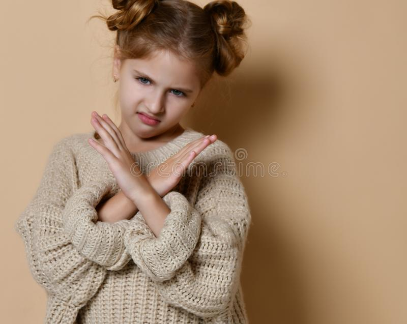 Portrait of serious, unhappy kid girl holding two arms crossed, gesturing no sign, looking away camera. On beige background stock images