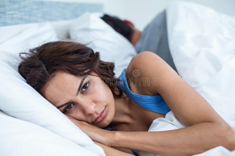 Portrait of serious woman lying on bed stock image