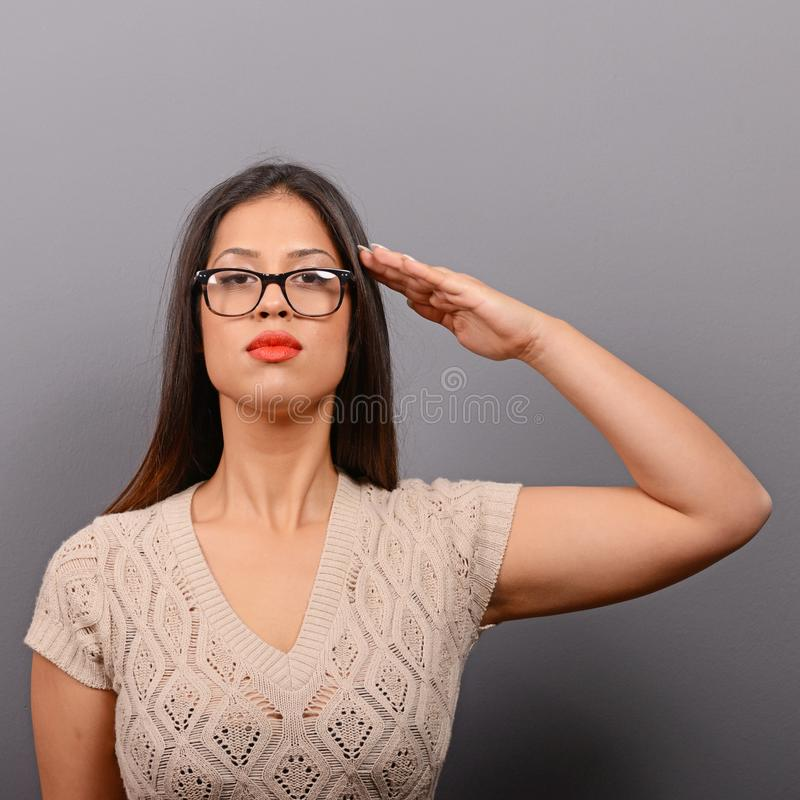 Portrait of serious woman saluting in casual clothes against gray background stock images