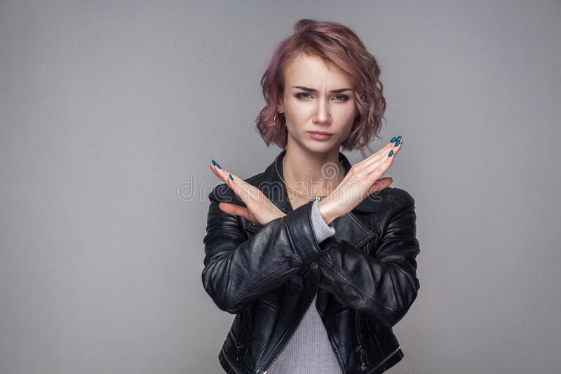 Portrait of serious woman with short hairs and makeup in casual style black leather jacket standing making X sign with her arms to. Stop doing something. indoor royalty free stock images