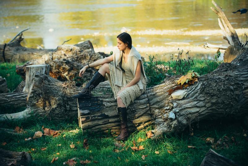 Portrait of serious woman on trunk wood. Young woman posing. Art work of romantic woman. Sensual model girl with smooth stock photos