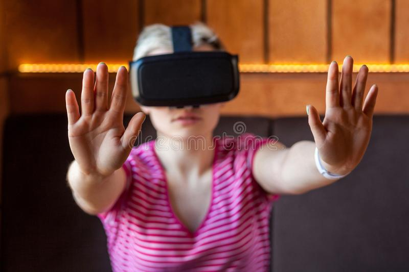 Portrait of serious young adult woman in pink t-shirt sitting in cafe, wearing virtual reality headset and watching video, playing stock photography