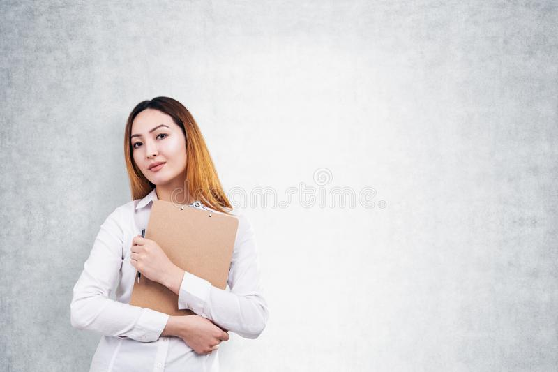 Serious Asian woman with clipboard and pen, mock up royalty free stock photo