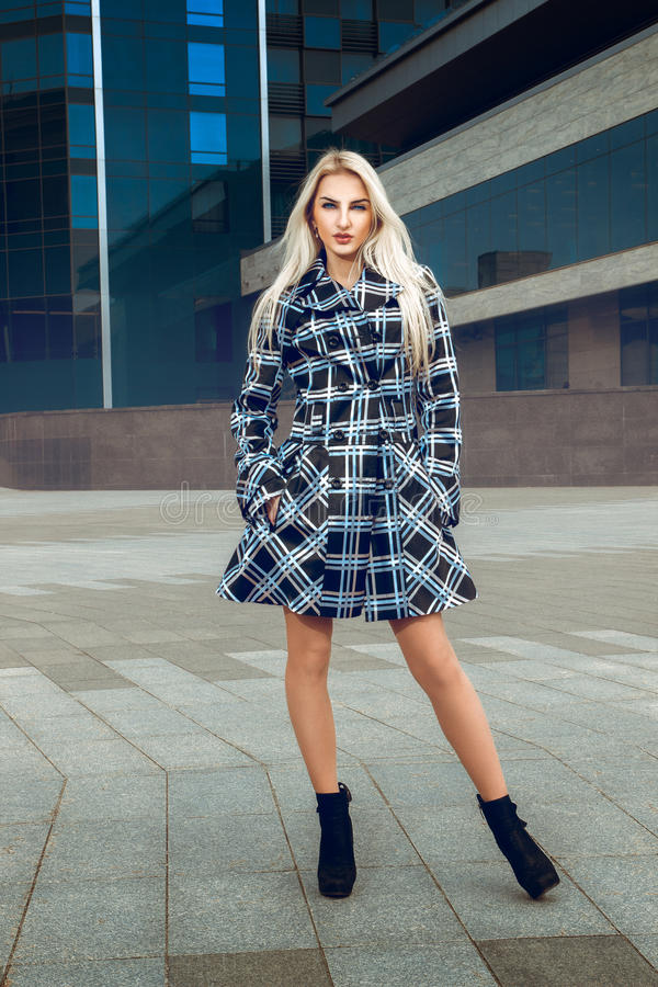 Portrait of serious young blonde model with blue eyes in the coat outdoors stock photo