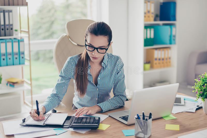 Portrait of serious young businesswoman accountant in formal wear and with pony tale, sitting at her work place and doing notes stock photos