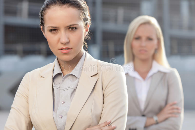 Portrait of serious young businesswoman with female colleague in background royalty free stock photography