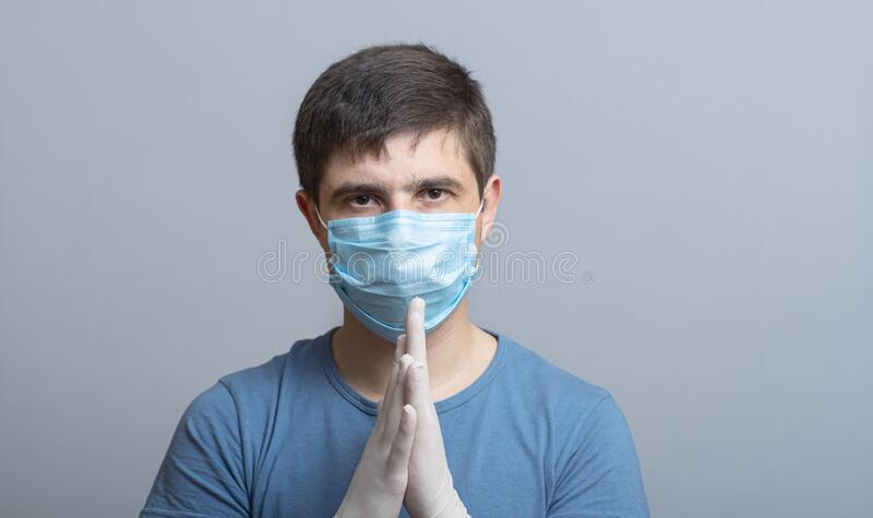 Portrait of a serious young doctor in protective medical mask in surgical gloves ready to operate on gray studio background,. Concept medicine and health stock photos