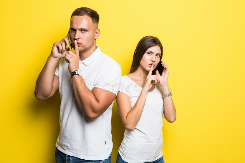 Portrait of serious young loving couple talking by mobile phones make silence gesture isolated over yellow background royalty free stock photo