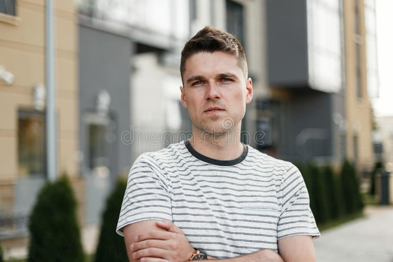Portrait of a serious young man with a fashionable hairstyle in a stylish striped t-shirt on the background of a modern building stock photo