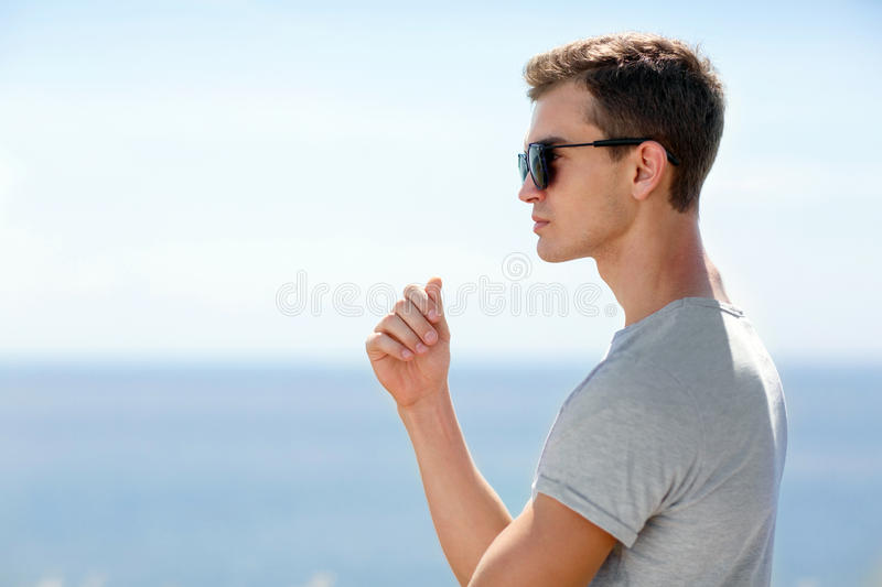 A portrait of a serious young man in sunglasses standing on a blurred sea background. A meditative guy. Copy space. royalty free stock images