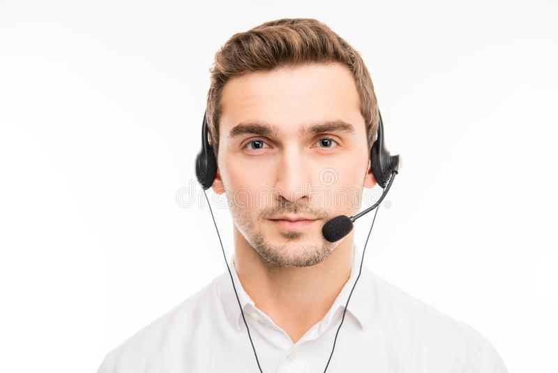 Portrait of serious young manager of call-center with headphones royalty free stock photo