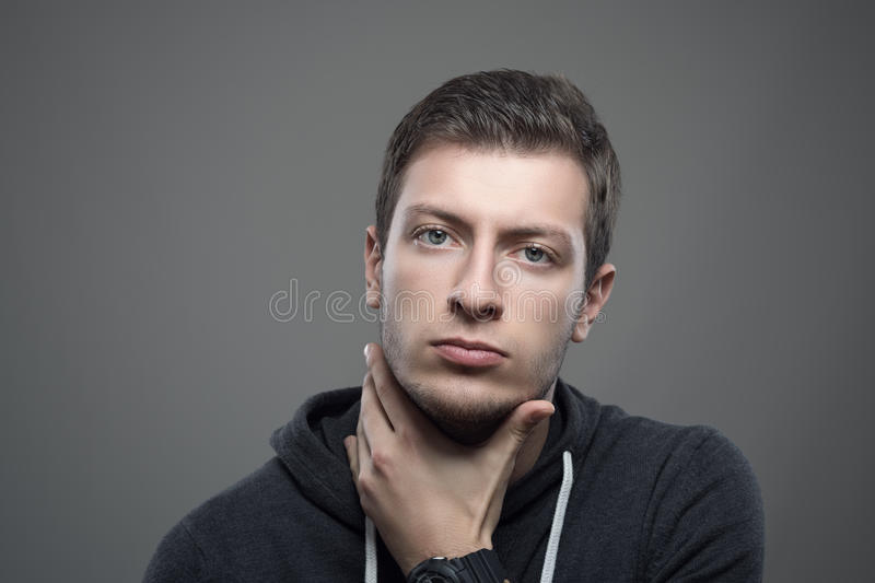 Portrait of serious young unshaven man with hand under chin. Moody portrait of serious young unshaven man with hand under chin looking at camera stock image